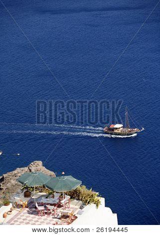 A tourism pleasure boat sailing across Santorini caldera, past a balcony at Oia (focus on the boat)