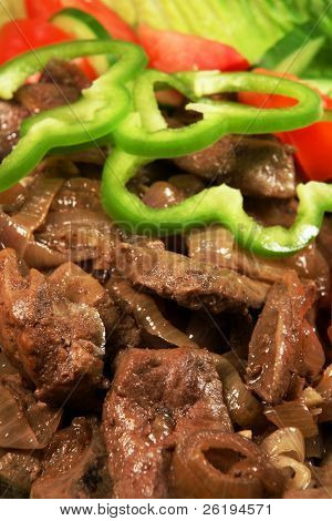 Liver and onions, close-up, with a salad.