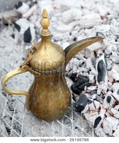 "A traditional Gulf brass ""dallah"" coffee pot, the Arab symbol of welcome, being kept warm beside burning charcoal."