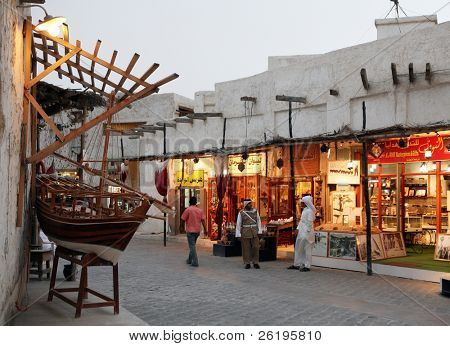 Lights come on in the tourist shops as evening falls over the Old Souq in Doha, Qatar.