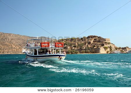 A pleasure boat takes day-trippers to Spinalonga island fortress, Crete - a Venetian castle that became  Greece's 20th Century leper colony