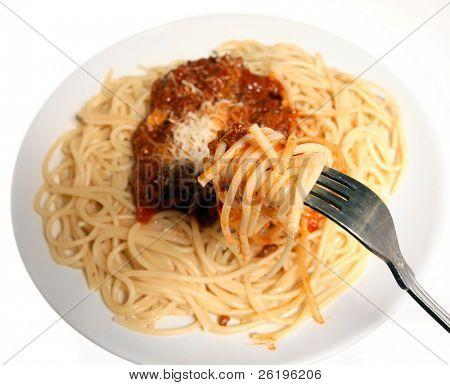 Bolonhesa espaguete sendo comida. O espaguete e molho na suspensão está em foco, a placa atrás s