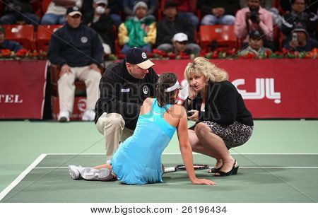 Serbian tennis star Ana Ivanovicgets assistance from WTA officials after twisting her ankle at the Qatar Total Open, Doha, February 20, 2008.