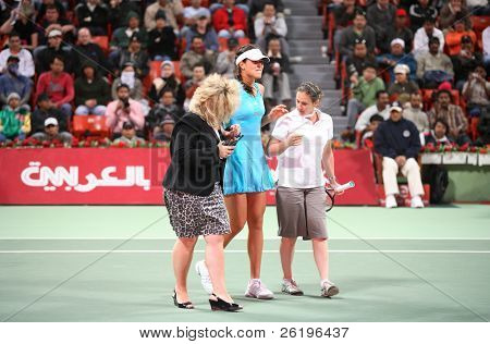 Serbian tennis star Ana Ivanovic, the world No 3, bites her lip in pain as she is helped off court by WTA officials after twisting her ankle at the Qatar Total Open, Doha, 2008.