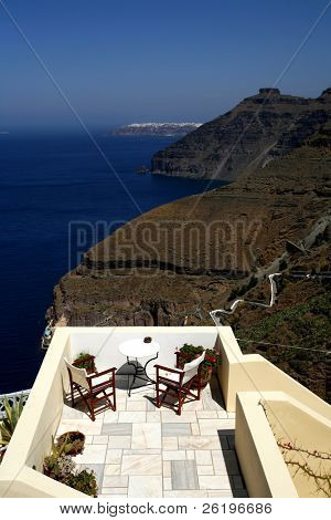 A balcony in Fira, Santorini, with a view of the dark volcanic cliffs, the steps to the harbour, the cable car and the sea in the caldera of the Cycladic island.