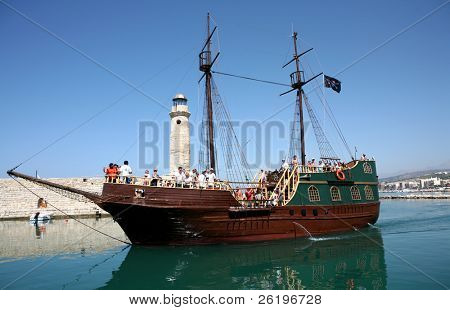 "A ""pirate"" ship packed with tourists (faces visible) sails into the Venetian Harbour at Rethymno, Crete, at the end of a day's outing."