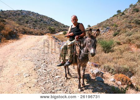 WHITE MOUNTAINS, CRETE - JULY 2008:  A peasant farmer on his donkey on the road between Kali Sykia and Saitoures. Donkeys, once ubiquitous, are now uncommon even in rural Crete.
