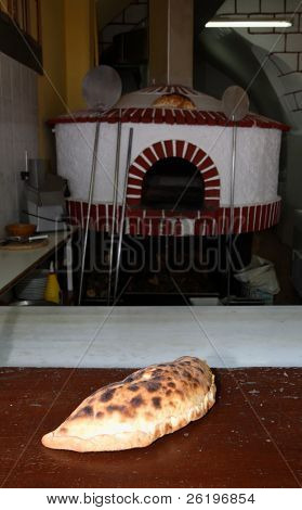 A calzone pizza on a baker's table with a traditional Mediterranean wood fired oven (sometimes called a pizza-oven), logs and pizza peels (paddles) behind. This bakery/taverna is in Rethymnon, Crete.