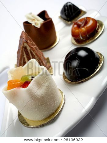 A group of varied petits fours gourmet cakes on a plate