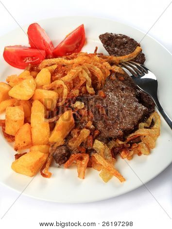 Traditional Austrian zweibelrostbraten, beef escalope with crispy fried onions, served with diced deep fried potatoes. The easily made meal is popular in Central European countries