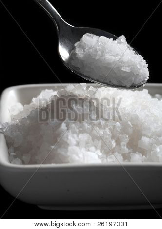 A spoon of coarse sea salt above a bowl of the same, with a black background.