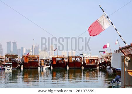 A view of the dhows in Doha harbour, with the Qatari flag flying from them and the new city skyline in the background.