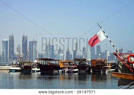 A view of the dhow harbour in Doha, Qatar, with the high-rise development across Doha Bay, a fusion of tradition and modernity which the Qataris are keen to develop The national flag is on the right.