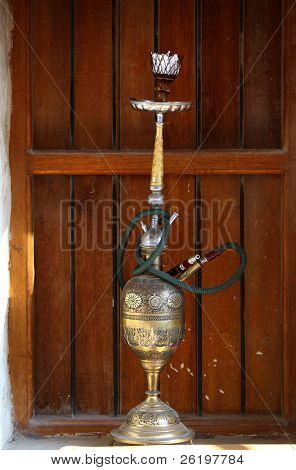 An old hookah or shisha pipe with a brass bowl on a window-cill with a wooden shutter behind, in Souq Waqif, Doha, Qatar