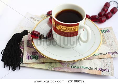 Worry beads and coffee - the Arab businessman's constant companions - on a pile of high denomination Qatari banknotes