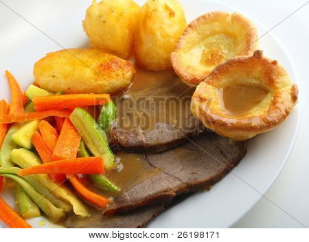 Traditional English meal of roast beef and yorkshire puddings (popovers), with julienned courgette (zucchini) and carrots, oven roasted potatoes and gravy.