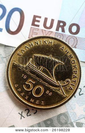 A 50 drachma coin, in circulation until the adoption of the single European currency, on a background of euro notes. The Greek adoption of the euro is now seen as a threat to the new currency
