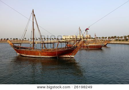 Various types of traditional Arab dhow moored off Doha Corniche. The type in the foreground is a boom, one of the larger vessels. Behind it is a jalibut and behind that the more common shuw'i .