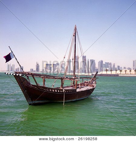 A Qatari sailing dhow, called a boom or boum, with the national flag flying and the Doha Skyline in the background. March 2010. Medium format film photograph, so has some grain.