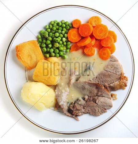 A plate of slided roast lamb, boiled peas, potatoes, carrots and gravy, viewed from above