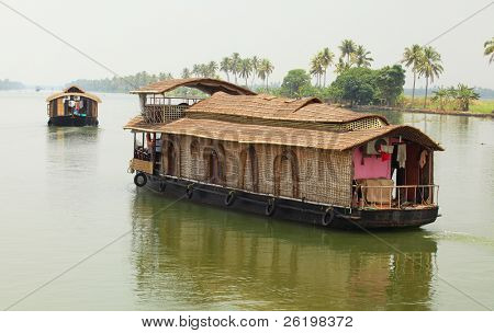 Thatched houseboats plying the Kerala Backwaters in India. River cruises are popular with foreign tourists and locals.