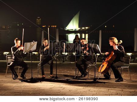 DOHA, QATAR - JANUARY 8: A string quartet performs against the backdrop of the Arabian Gulf and an Arab dhow as part of Qatar's celebration on hosting the Asian Cup, January 8, 2011
