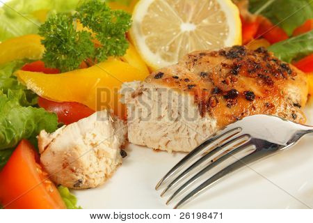 A sautéed peppered lemon-marinaded chicken breast served with a slice of lemon and salad vegetables.