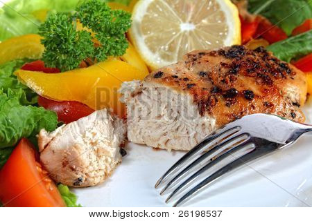 A meal of marinated pepper chicken breast served with french fries and a salad of lettuce, tomato, rocket, capsicum and a slice of lemon.