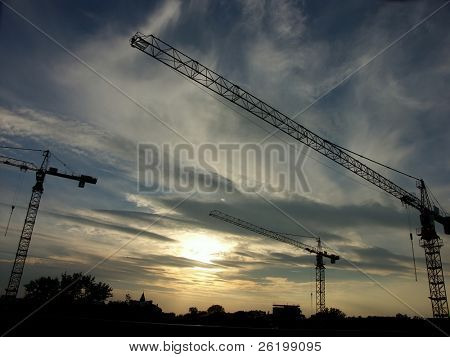 Jib cranes against the sun setting