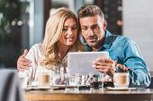 Happy Affectionate Couple Using Digital Tablet In Cafe poster