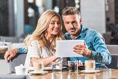 Affectionate Adult Couple Using Tablet At Table In Cafe poster