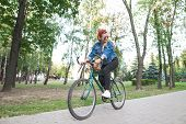 Young Happy Girl In Stylish Clothes Rides A Green Bike In The Park. Student Girl Is Actively Resting poster