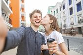 Portrait Of A Lovers Of A Young Couple Takes Selfie On The Street Of The Town. Smiling Young Man Wit poster
