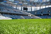 Grass On Stadium In Sunlight. Closeup Of A Green Football Field. Wet Stadium Grass In The Morning Li poster