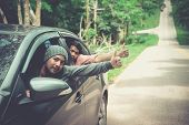 Men In Car Road Trip Waving Out The Window Smiling.  Two Young Asian Friend Leaning Out Of Car Windo poster