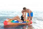 Happy Young Couple In Beachwear Swimming With Inflatable Mattress In Sea poster