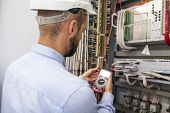 Young Adult Electrician Builder Engineer Inspecting Electric Equipment In Distribution Fuse Box. Ele poster