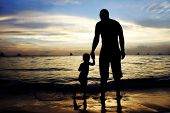 father and son on sunset sea and sky background