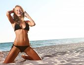 foto of woman body  - young happy woman in black bikini on beach - JPG