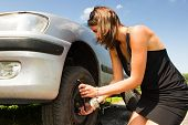 Young woman changing a flat tire on her car