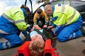 image of neck brace  - Two paramedics and a fireman working together to help an injured woman at the site of a car crash - JPG