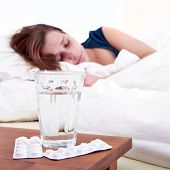 stock photo of ibuprofen  - Glass of water and two strips of pills on a bedside table - JPG