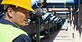 foto of blue-collar-worker  - Maintenance engineer at the waste water management system of a huge factory - JPG