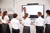 Male High School Tutor Teaching High School Students Wearing Uniforms In Science Class poster
