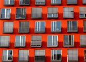 Image Of Red High Rise Building With Windows And Balconies And Blinds poster