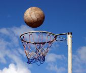 stock photo of netball  - A netball frozen mid air above the goal - JPG