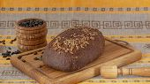 Fresh Whole Grain Bread With Seeds On A Wooden Board, Mortar With Sunflower Seeds. Rye Bread With Su poster