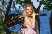 Woman Playing Acoustic Guitar In Park poster