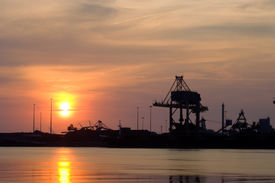 picture of iron ore  - Steelworks at sunset with a huge crane used to unload the raw materials - JPG