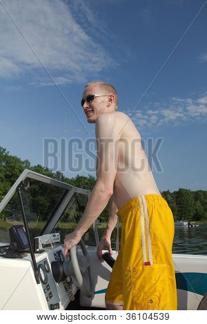 Young Man Standing, Driving Speed Boat On Lake With Blue Sky Above